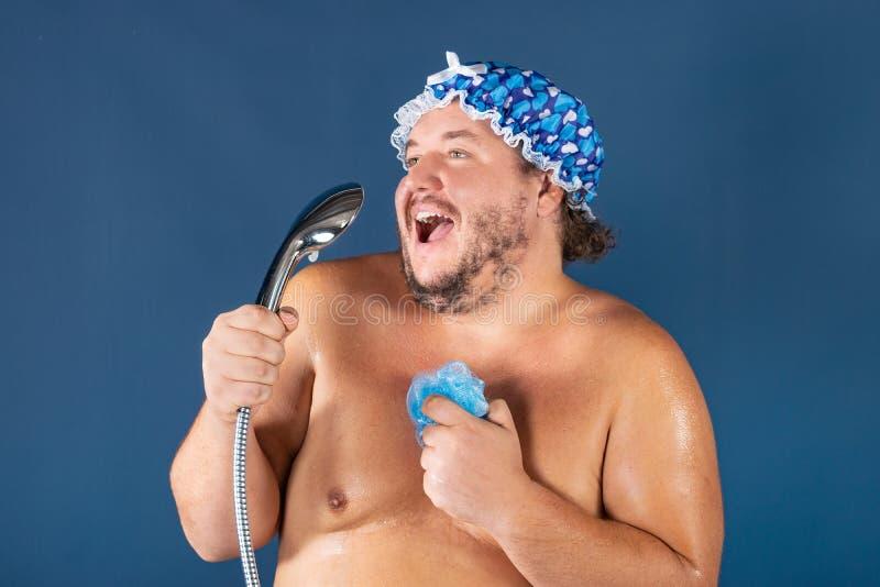 Le gros homme drôle dans le chapeau bleu chantent dans la douche image stock