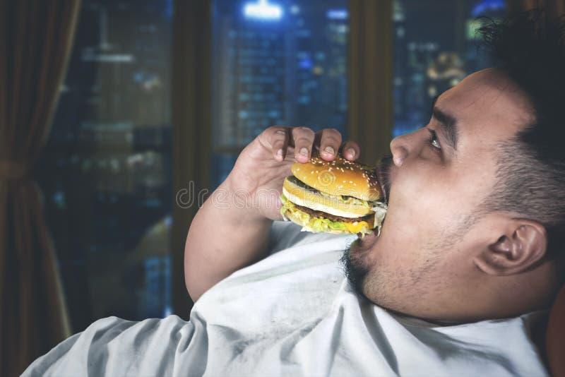 Le gros homme glouton apprécie un hamburger dans l'appartement photographie stock