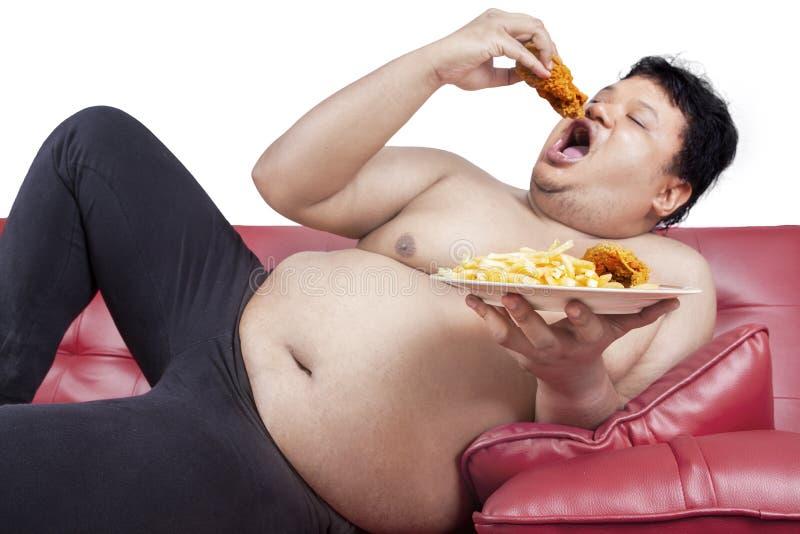 Le gros homme mange de la nourriture industrielle 2 image libre de droits