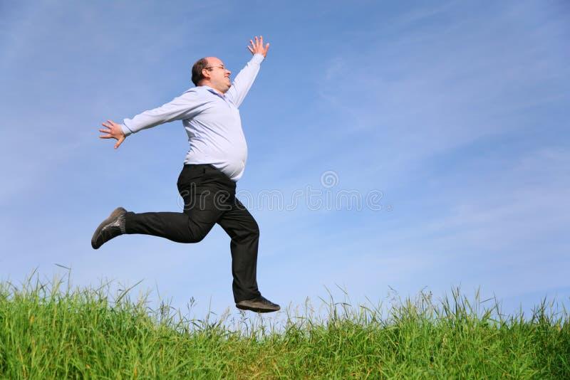 Le gros homme saute sur le pré photos stock