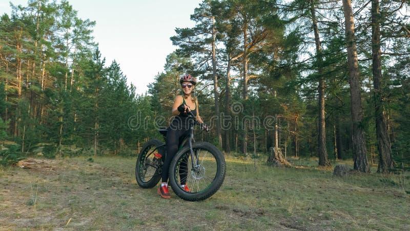 Le gros vélo a également appelé le vélo de fatbike ou de gros-pneu dans l'équitation d'été dans la forêt image libre de droits