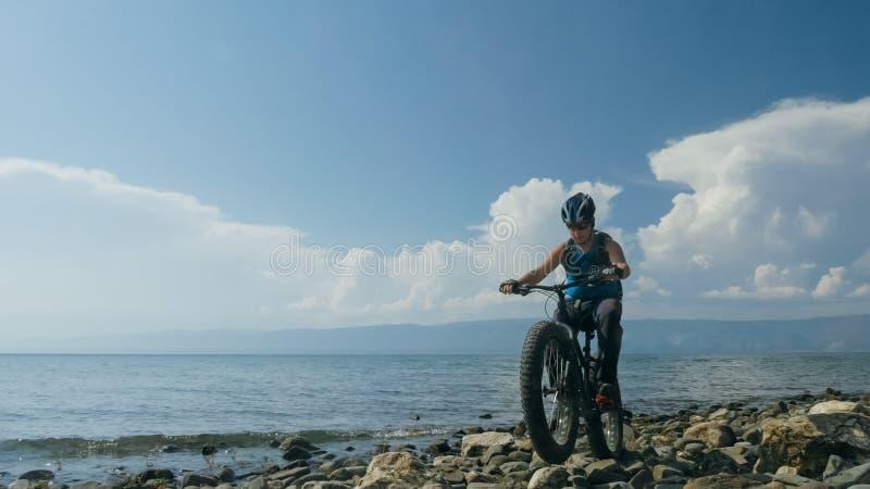 Le gros vélo a également appelé le vélo de fatbike ou de gros-pneu en été conduisant sur la plage photographie stock libre de droits