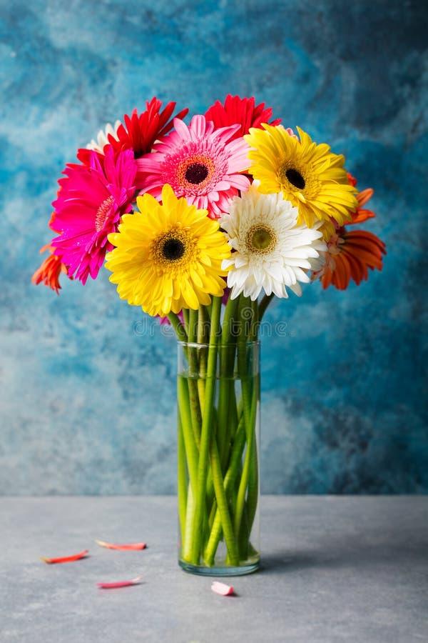 Le groupe coloré de gerbera fleurit dans un vase en verre Fond de pierre bleue Copiez l'espace photographie stock