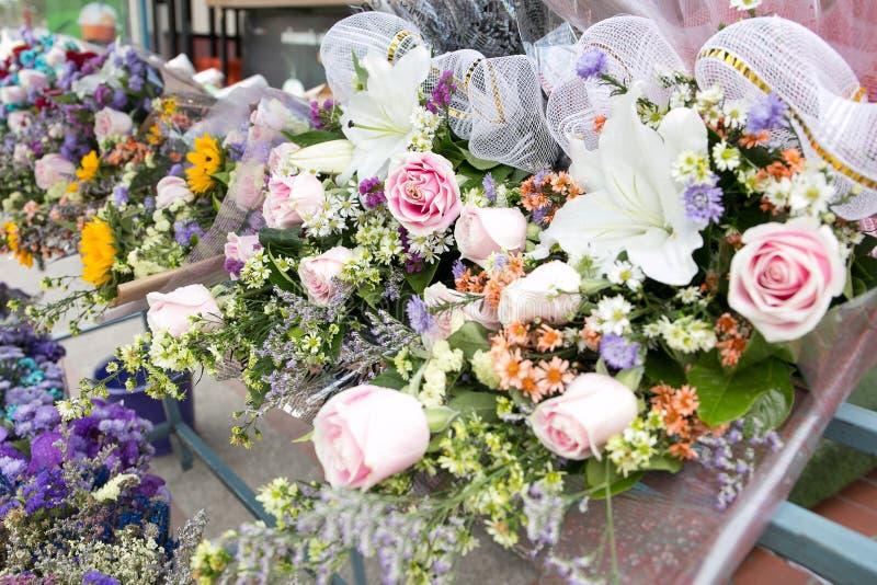 Le groupe coloré de rose de rose et de lis blanc fleurit sur une étagère pour la vente, Bangkok, Thaïlande image stock