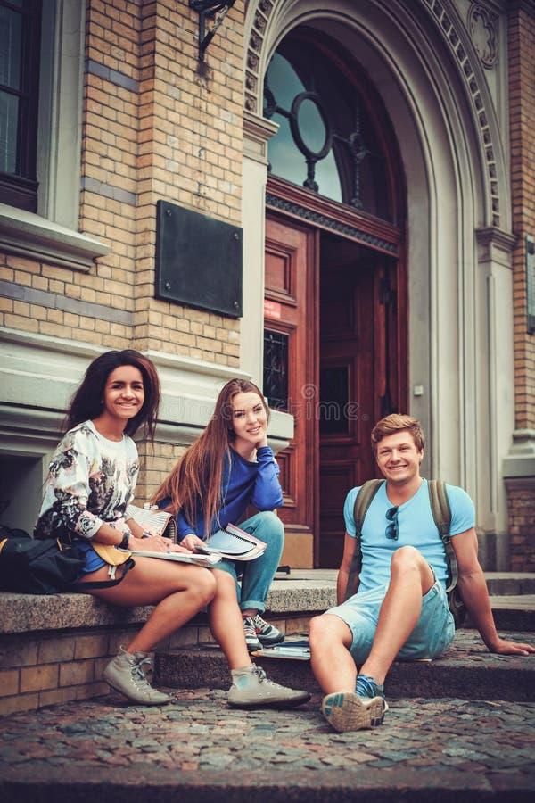 Le groupe d'étudiants ethniques multi s'approchent de l'entrée de bâtiment d'université image stock