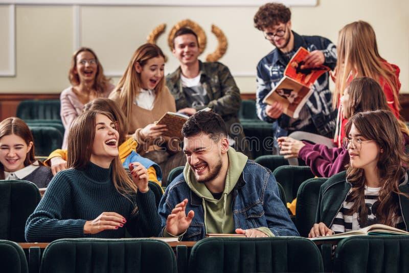 Le groupe d'étudiants heureux gais s'asseyant dans une salle de conférences avant leçon photos libres de droits