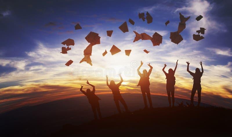 Le groupe d'étudiants heureux montrent le succès de papier d'éducation soulevant des mains avec des dossiers sur la montagne photos stock