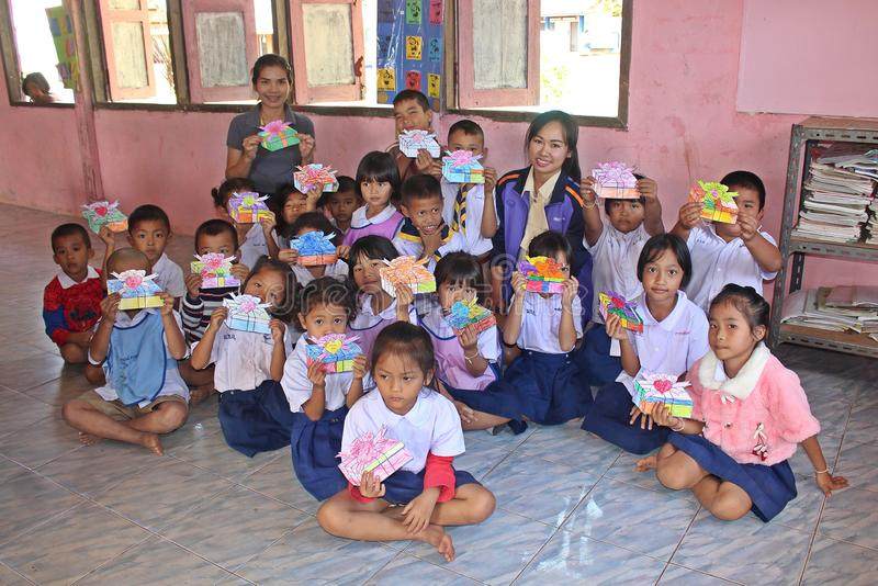 Le groupe d'étudiants primaire asiatique montre le dessin de cadeau photographie stock libre de droits