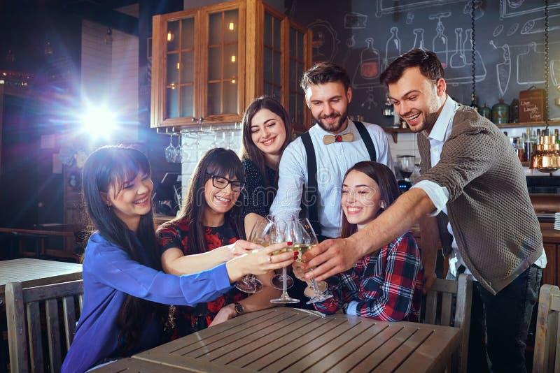 Le groupe d'amis célèbrent ayant l'amusement causant avec le glasse photos libres de droits