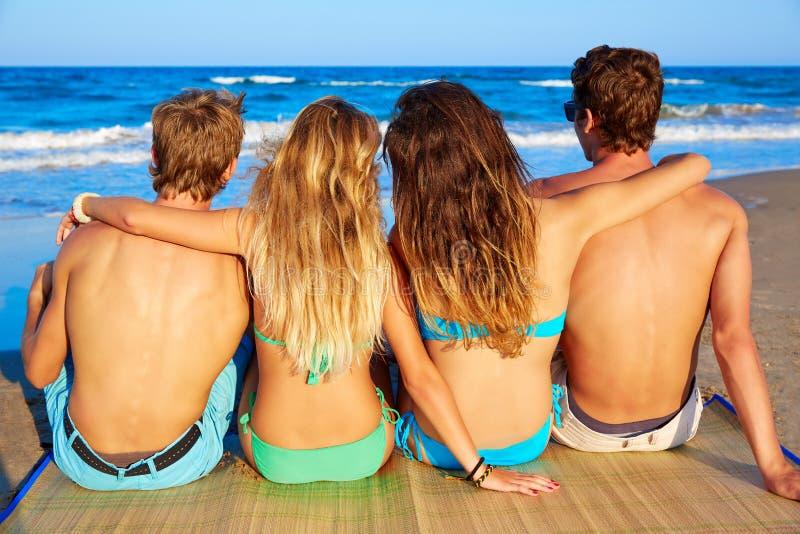 Le groupe d'amis couple se reposer à l'arrière de sable de plage photo stock