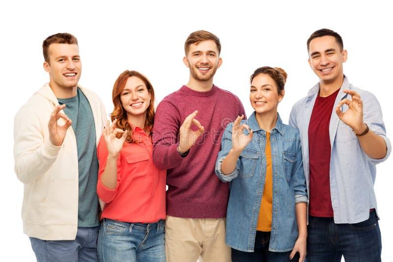 Le groupe d'amis de sourire montrant des mains d'ok signent photo stock