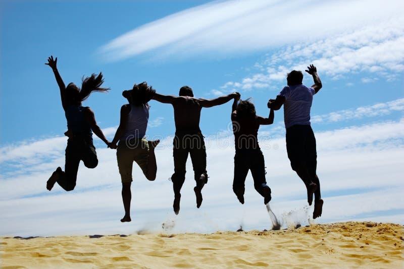 Le groupe d'amis saute sur le sable, vue arrière image libre de droits