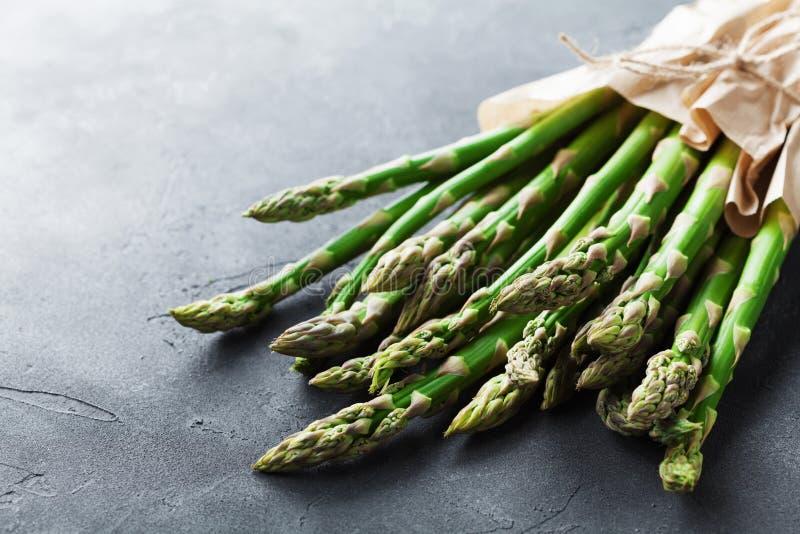 Le groupe d'asperge verte fraîche pousse dans le sac d'épicerie de papier de métier sur la table en pierre Nourriture saine et de images stock