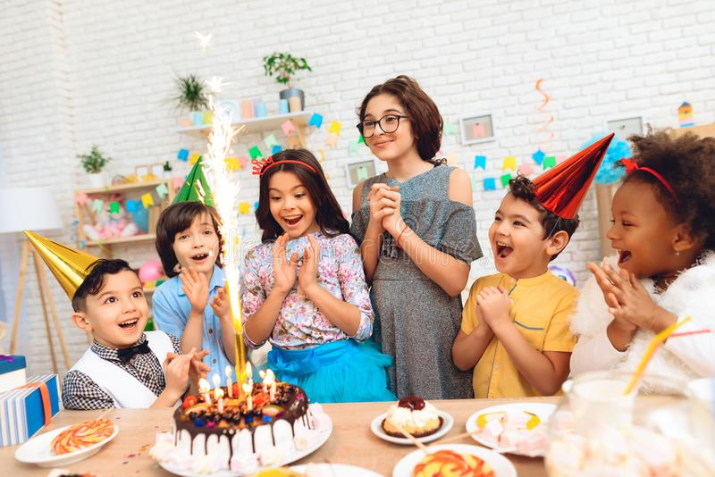 Le groupe d'enfants se réjouissent du gâteau avec les bougies brûlantes occasionnellement de l'anniversaire Concept d'anniversair image libre de droits