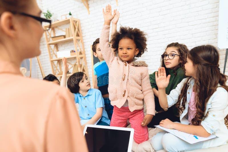 Le groupe d'enfants tirent des mains à la question du ` s de professeur de réponse à l'école primaire image libre de droits