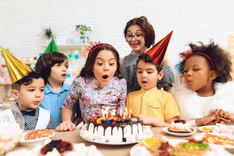 Le groupe d'enfants va souffler des bougies sur le gâteau Partie de joyeux anniversaire photographie stock
