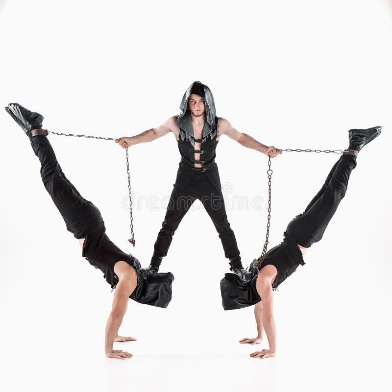 Le groupe d'hommes caucasiens acrobatiques gymnastiques sur la pose d'équilibre images libres de droits
