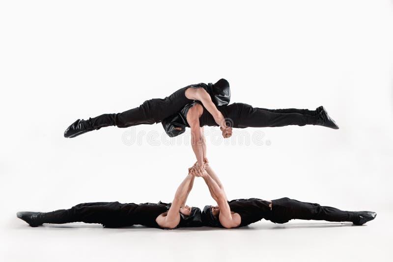 Le groupe d'hommes caucasiens acrobatiques gymnastiques sur la pose d'équilibre photos stock
