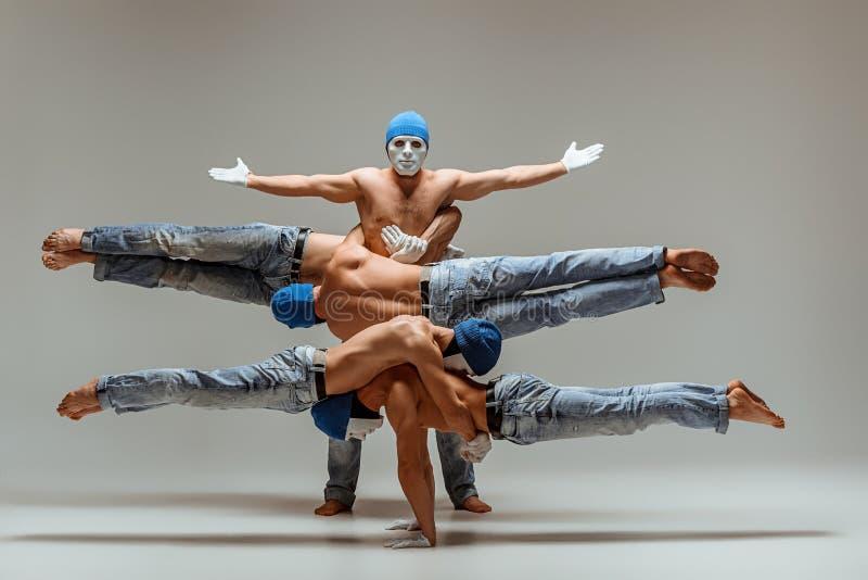 Le groupe d'hommes caucasiens acrobatiques gymnastiques sur la pose d'équilibre photos libres de droits