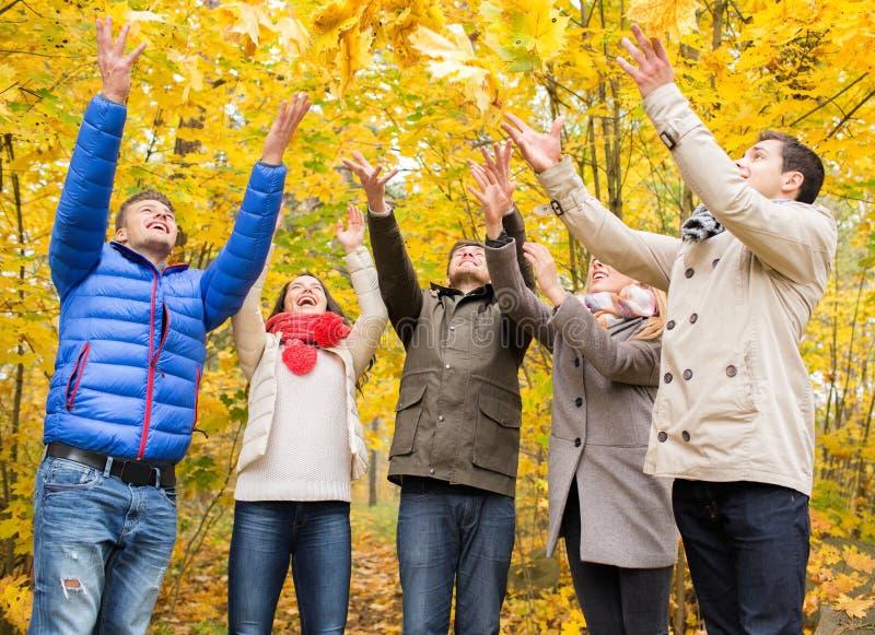 Le groupe d'hommes de sourire et les femmes en automne se garent photo libre de droits