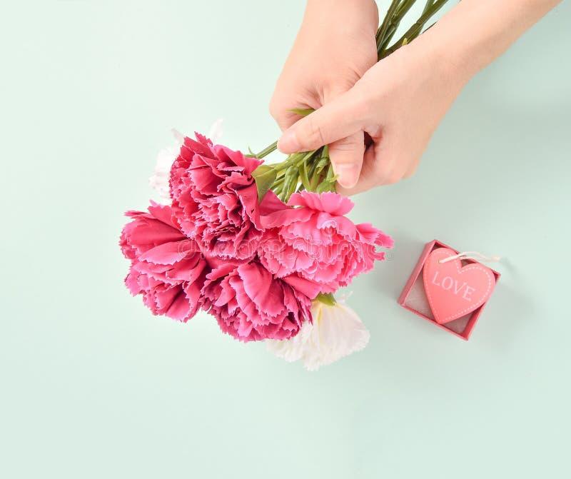 Le groupe d'oeillet de jour du ` s de mère de mai de bouquet de fleurs holded par la main du ` s de mère photographie stock libre de droits