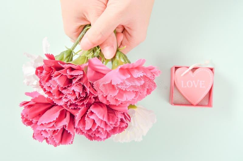 Le groupe d'oeillet de jour du ` s de mère de mai de bouquet de fleurs holded par la main du ` s de mère photos stock