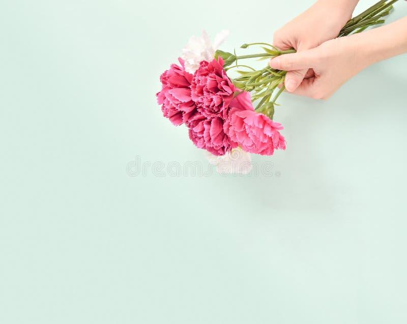 Le groupe d'oeillet de jour du ` s de mère de mai de bouquet de fleurs holded par la main du ` s de mère, la vue supérieure, blan photos libres de droits