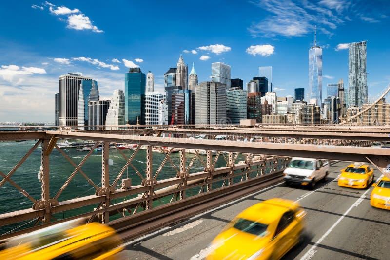 Le groupe de cabines jaunes typiques brouillées de New York croisant le pont de Brooklyn avec l'horizon de Manhattan avec le ciel images stock