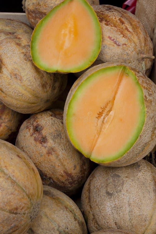 Le groupe de cantaloups organiques, et un ont coupé dans la moitié montrant sa chair orange, montrée en vente sur le marché de l' photo stock