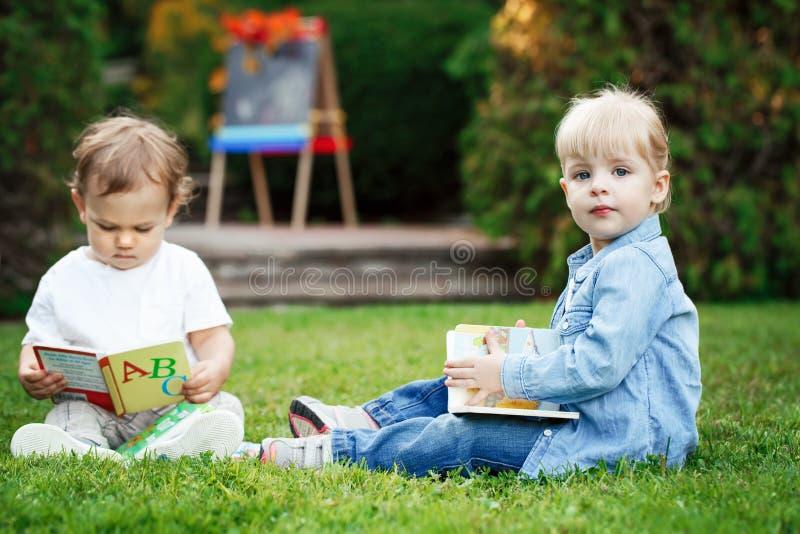 Le groupe de deux enfants caucasiens blancs d'enfant en bas âge badine le garçon et la fille s'asseyant dehors dans l'herbe en pa photo stock