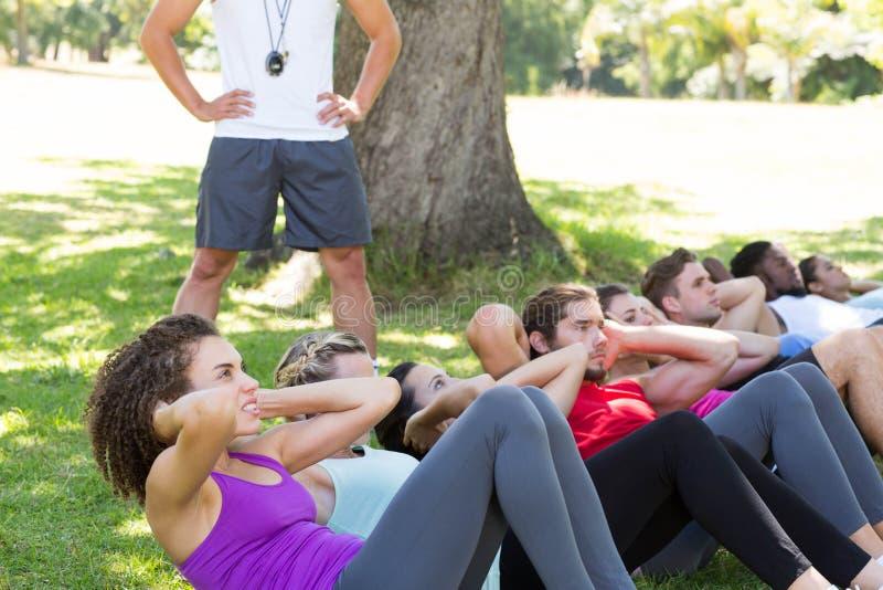 Le groupe de forme physique que faire se reposent se lève en parc avec l'entraîneur photos libres de droits