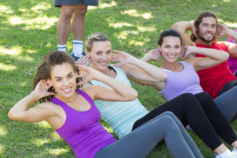 Le groupe de forme physique que faire se reposent se lève en parc avec l'entraîneur images libres de droits