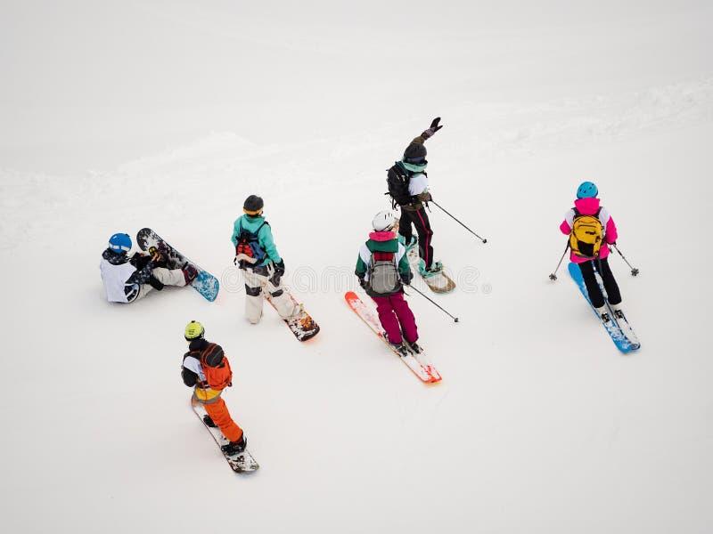 Le groupe de freeriders de skieurs et de surfeurs de filles se tiennent dans la neige et inspectent la pente images stock