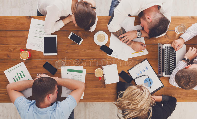 Le groupe de gens d'affaires épuisés dorment dans le bureau, vue supérieure photo stock