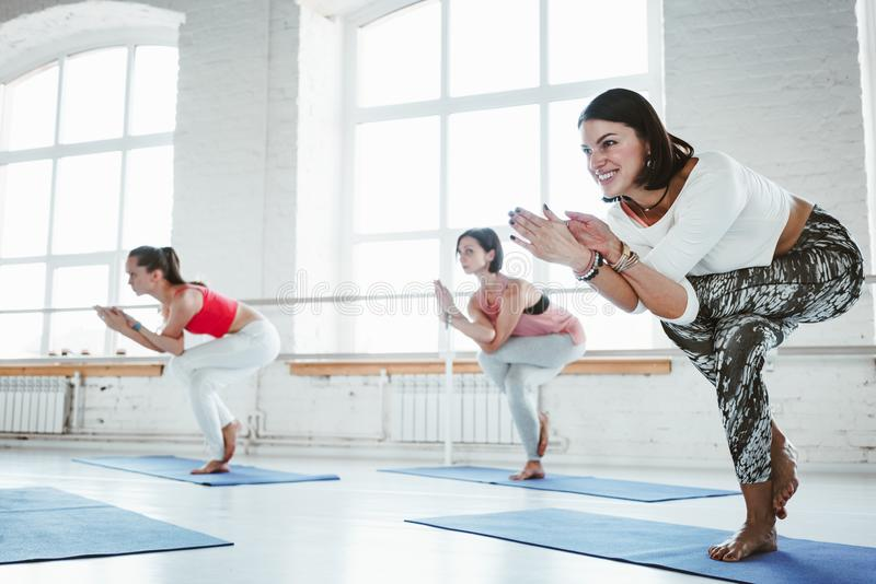 Le groupe de jeune yoga heureux de pratique en matière de femme pose la classe d'intérieur photo libre de droits