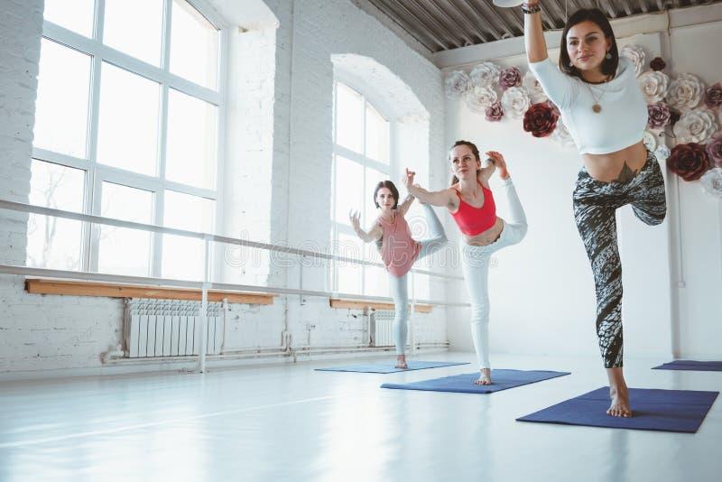 Le groupe de jeune yoga heureux de pratique en matière de femme pose la classe d'intérieur formation de groupe images stock