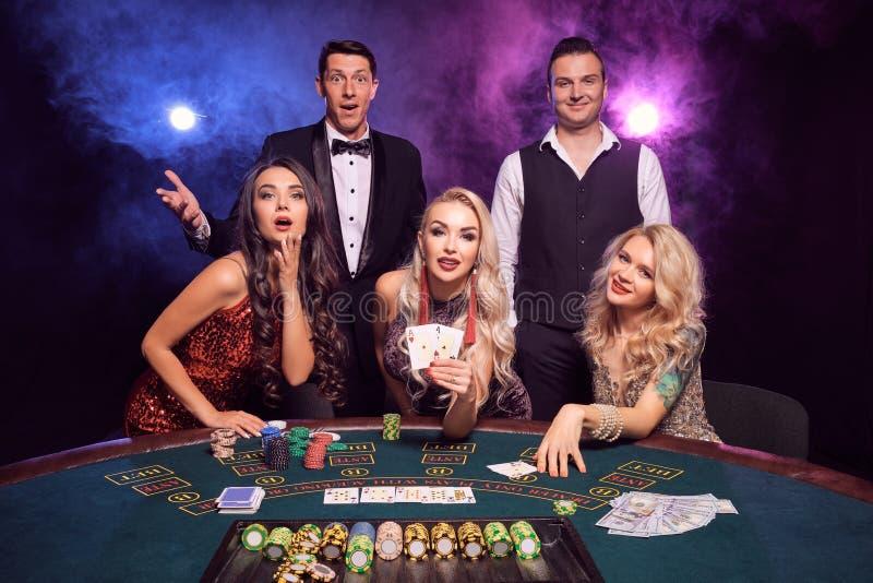 Le groupe de de jeunes amis riches jouent au poker à un casino photographie stock libre de droits