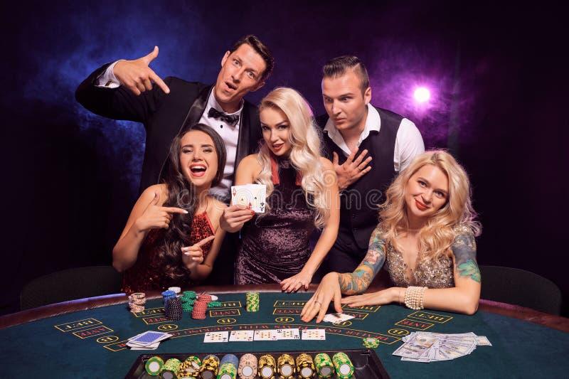 Le groupe de de jeunes amis riches jouent au poker à un casino image libre de droits