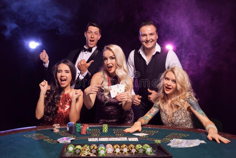 Le groupe de de jeunes amis riches jouent au poker à un casino photos libres de droits