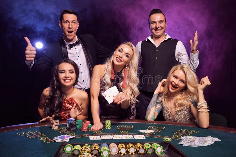 Le groupe de de jeunes amis riches jouent au poker à un casino photo libre de droits