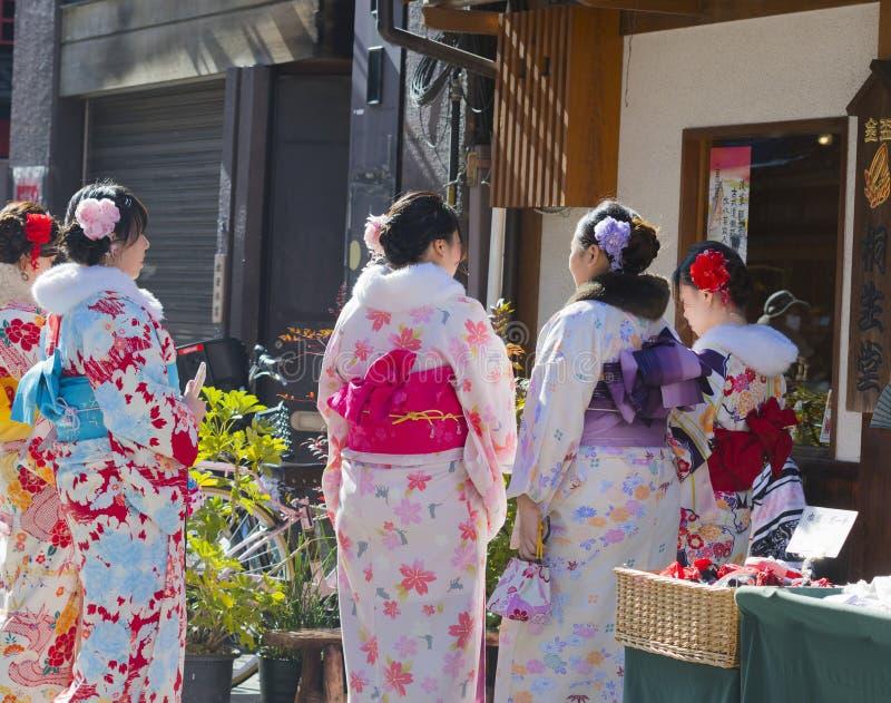 Le groupe de jeunes femmes japonaises s'est habillé dans le kimono, faisant des emplettes à la stalle du marché, Asakusa, Japon,  photographie stock libre de droits