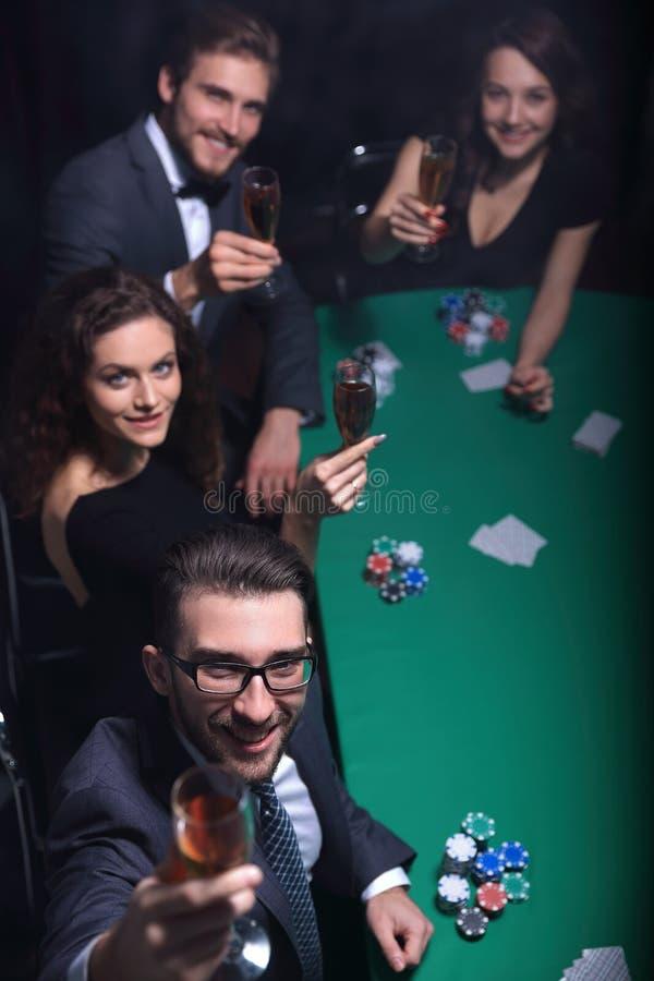 Le groupe de jeunes riches joue le tisonnier dans le casino photographie stock libre de droits