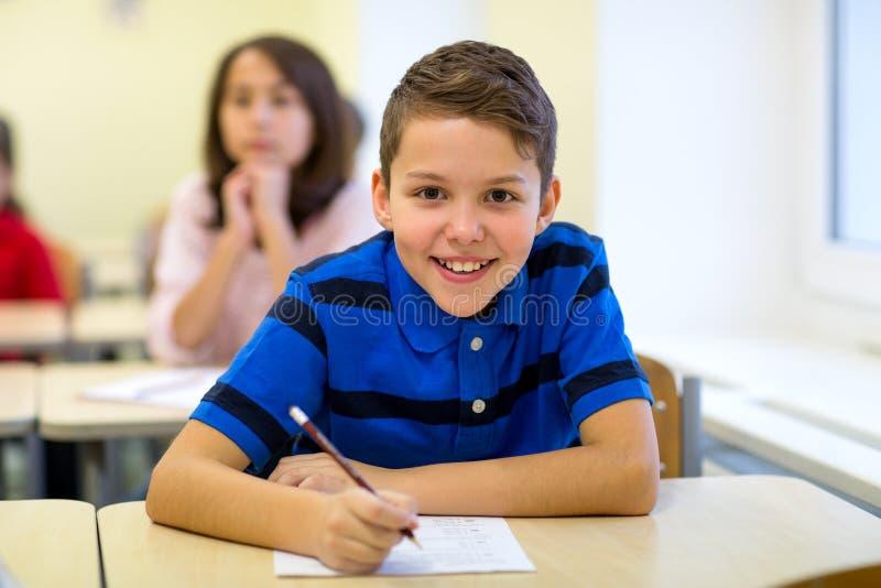 Le groupe de l'école badine l'essai d'écriture dans la salle de classe photos stock