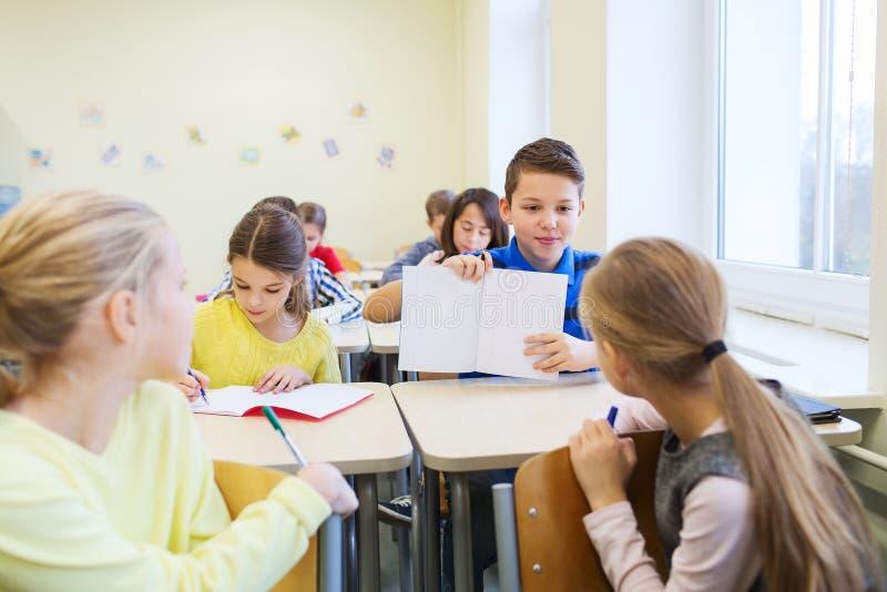Le groupe de l'école badine l'essai d'écriture dans la salle de classe photos libres de droits