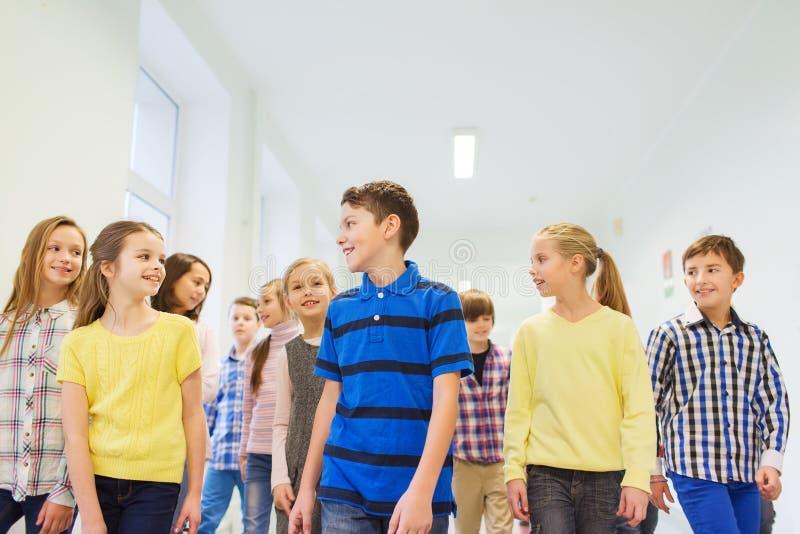 Le groupe de l'école de sourire badine la marche dans le couloir images stock
