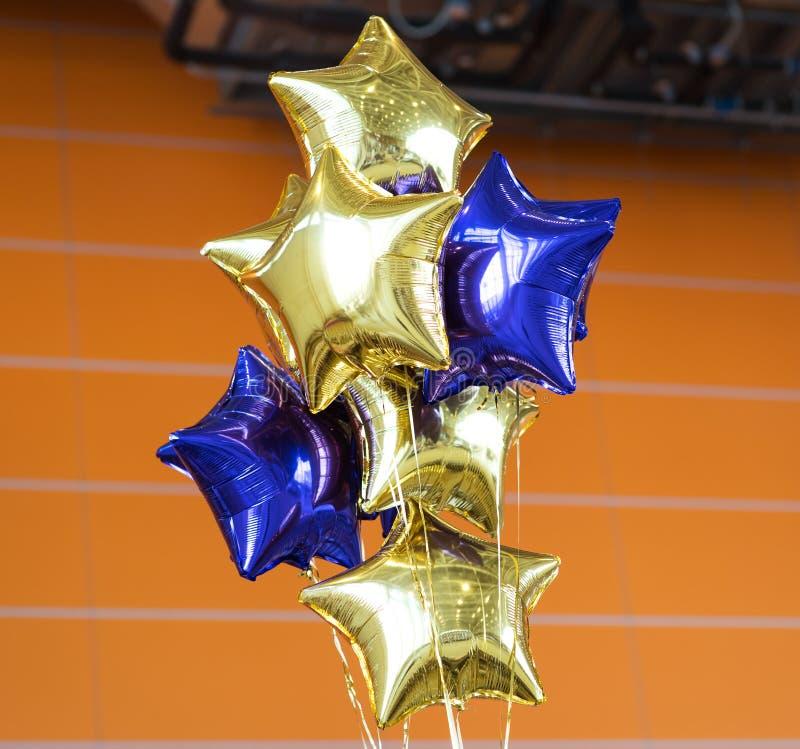 Le groupe de Mylar bleu et jaune monte en ballon avec le mur orange photographie stock