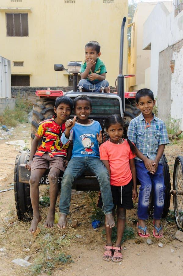 Le groupe de pauvres enfants indiens s'assied sur le tracteur dedans dehors 11 février 2018 Puttaparthi, Inde images libres de droits