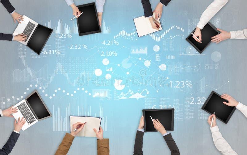 Le groupe de personnes avec des dispositifs dans des mains teamworking sur des ordinateurs portables, comprimés et établissent le image stock