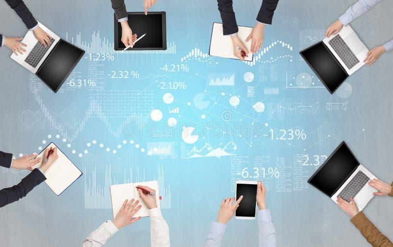 Le groupe de personnes avec des dispositifs dans des mains teamworking sur des ordinateurs portables, comprimés et établissent le photographie stock libre de droits