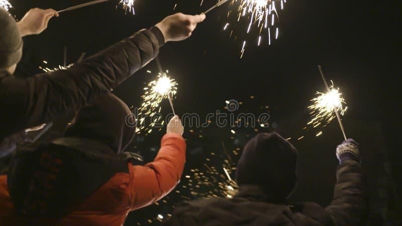 Le groupe de personnes célèbrent la nouvelle année sur la rue avec des cierges magiques action Heureusement et joyeux, les gens c photographie stock